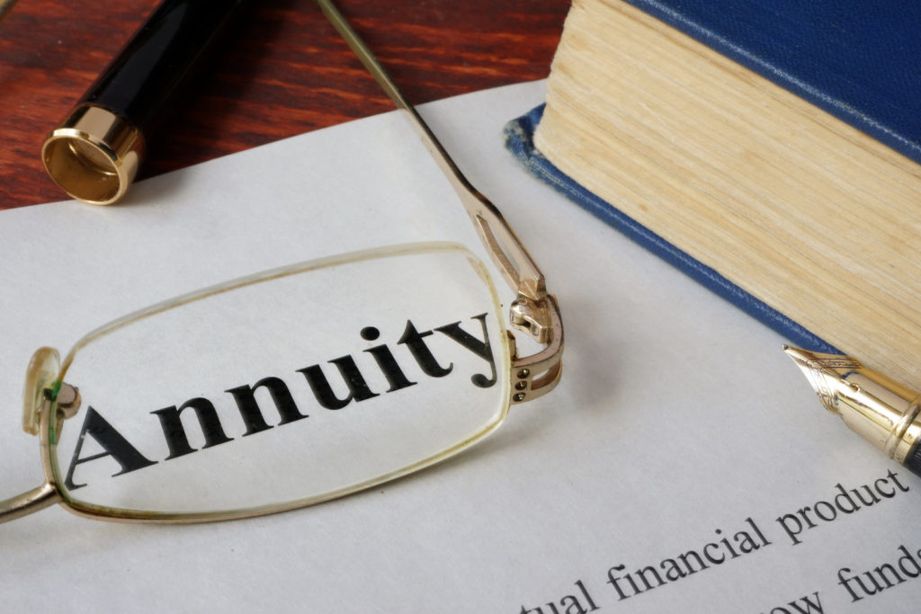Annuity Scams - Annuity contract with a book, pen and reading glasses sitting on top of it