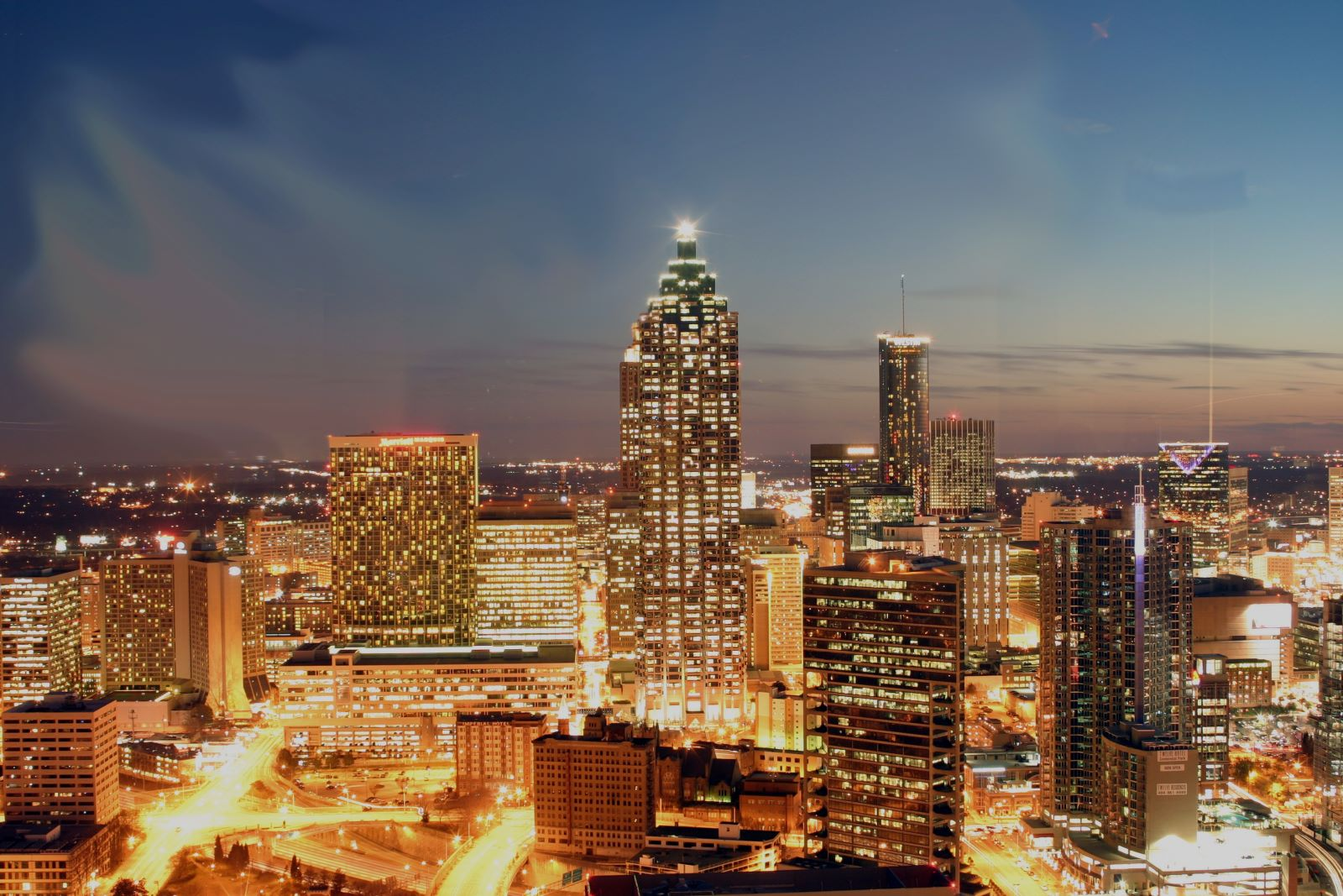 Downtown Atlanta at dusk with the city all lit up, dark blue skies with the sunset at the far edge of the city