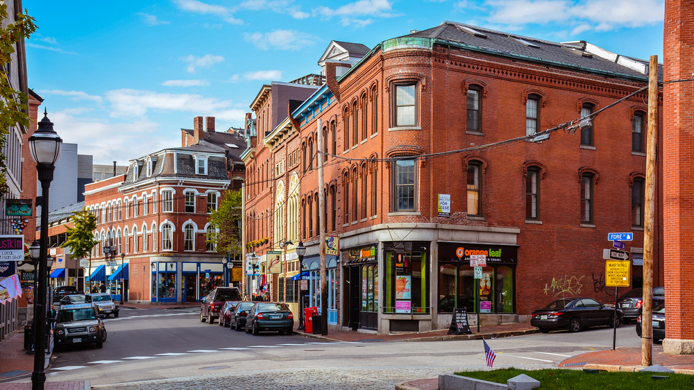 Downtown Portland Maine showing a brick corner building, other buildings, and some cars