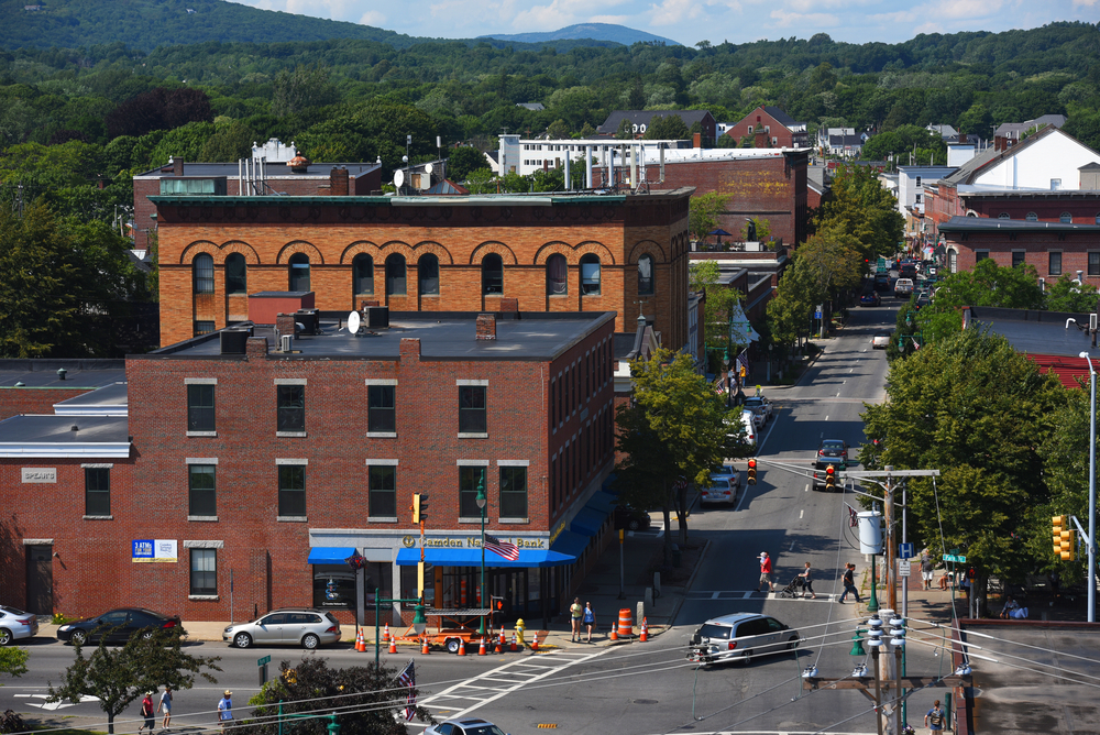 Downtown in Rockland Maine, with cars traveling down the road