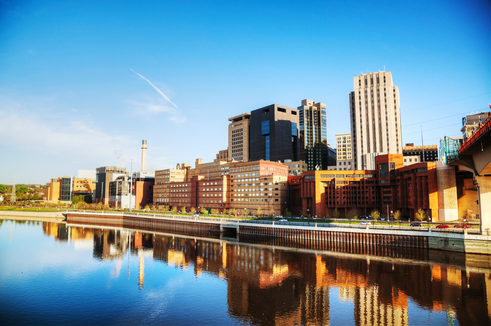 Downtown st paul along the mississippi river with blue skies and the cities reflection along the water