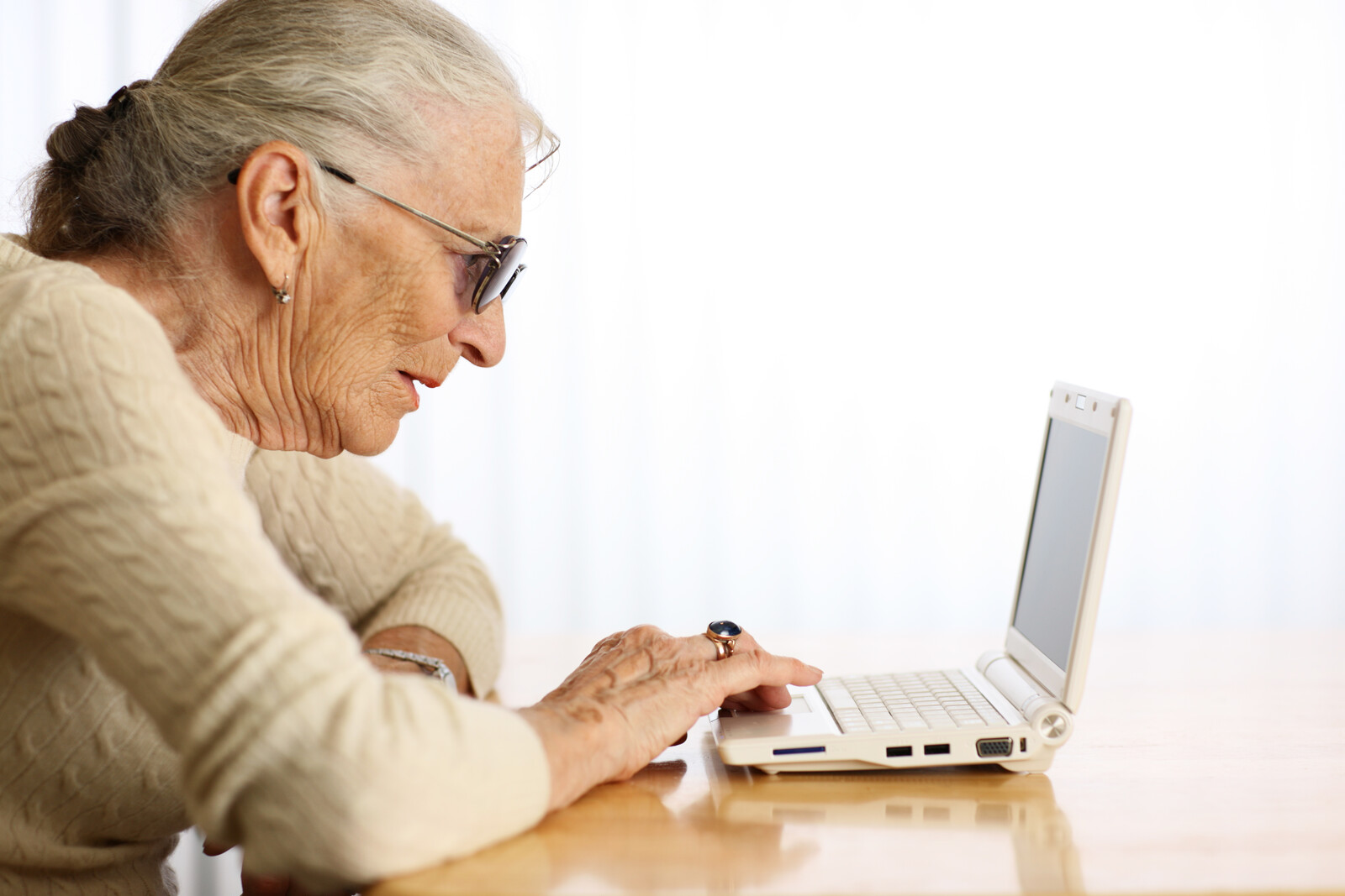 Elderly woman typing on portable laptop computer
