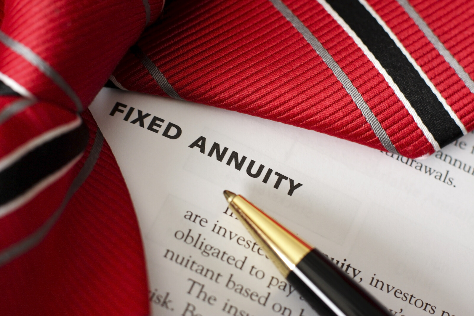 Document that says Fixed annuity with a red neck tie laying over part and a ball point pen pointing at the words
