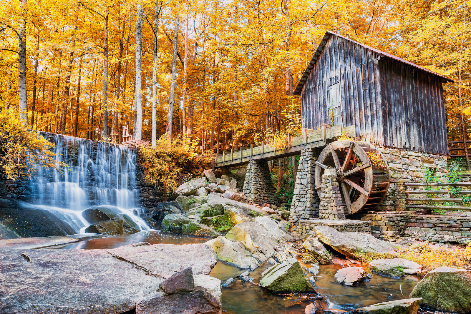 Autumn historic mill with waterfall surrounded by golden trees in Marietta City