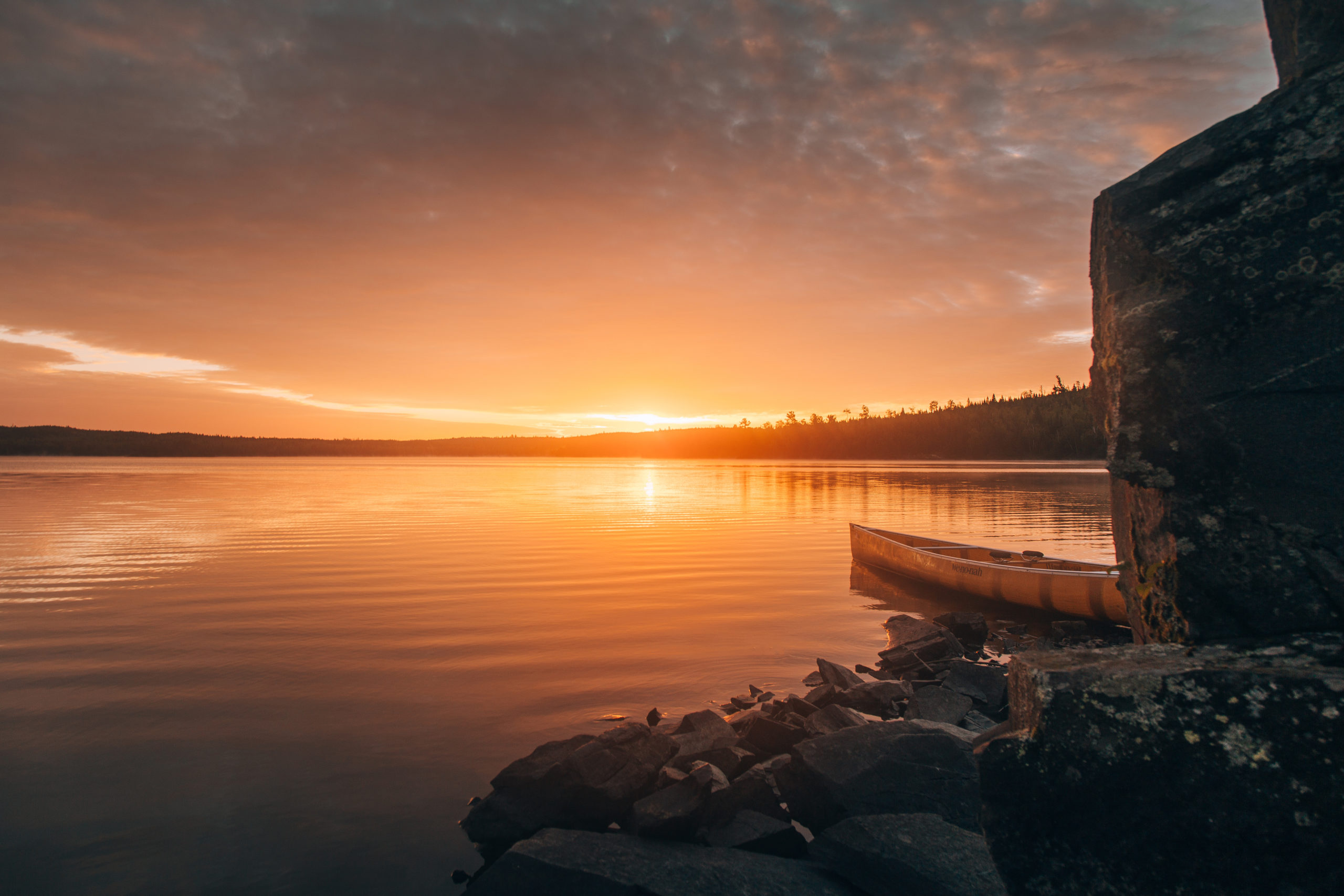 Places to Retire in Minnesota -  Lake at sunset with orange skies reflecting off the lake and a canoe resting on the shore, with trees and rocks surrounding the water
