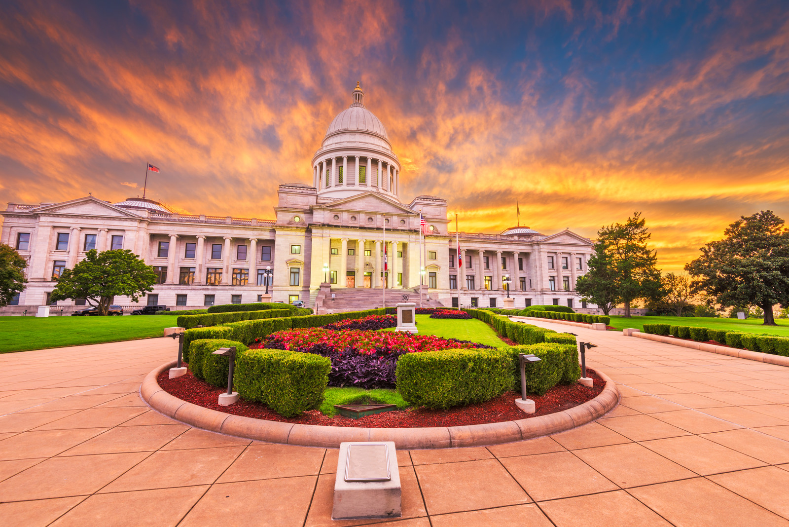 Top 5 Places to Retire in Arkansas- Capital building in little rock Arkansas at sunrise with a  manicured garden with flowers in the middle