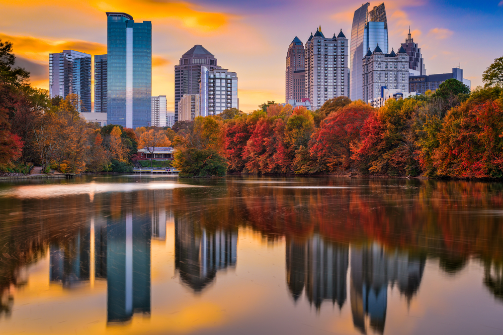 The Atlanta skyline over autumn trees and a lake, where the buildings are reflected on the lake