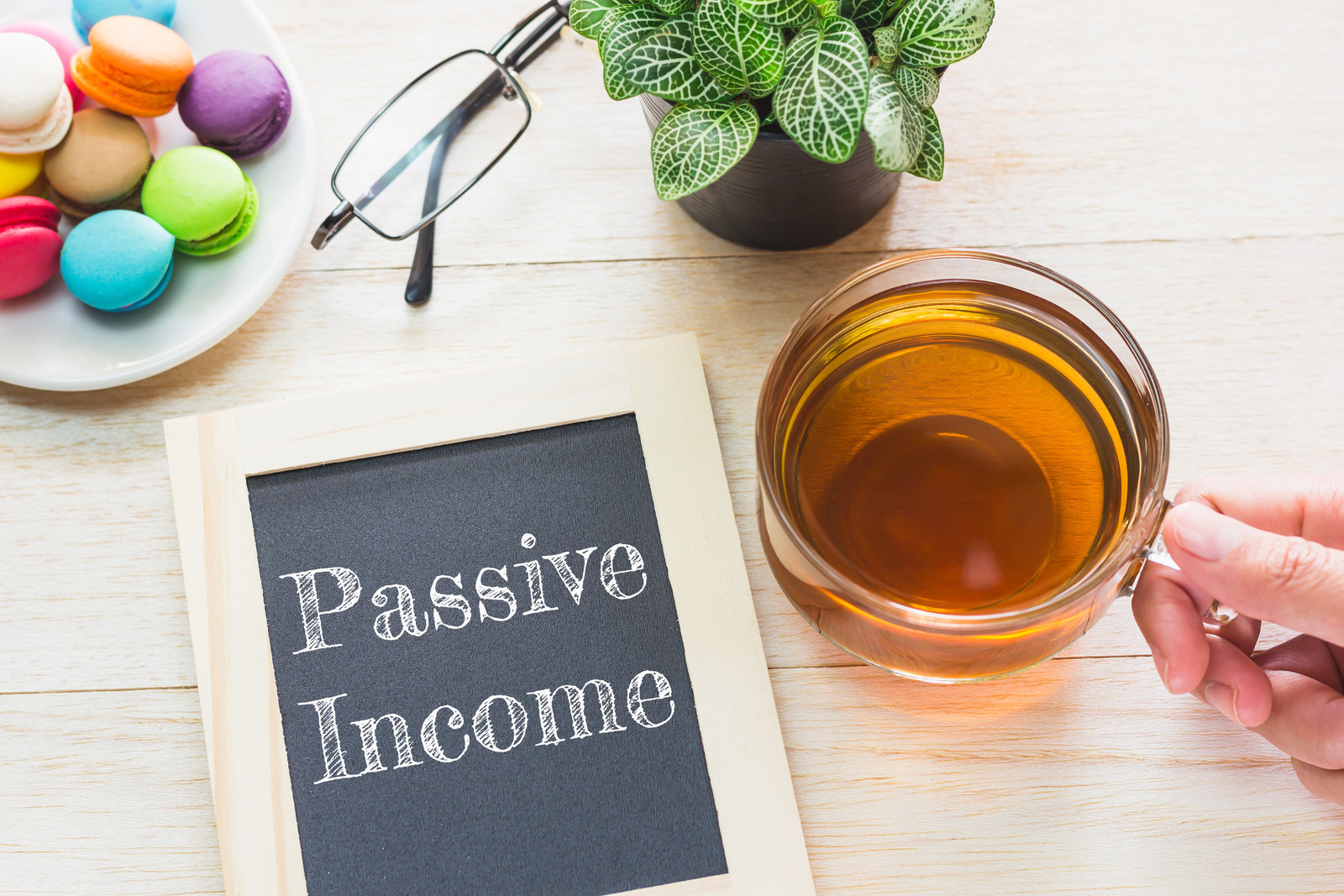 Passive income message written on a blackboard. macaroons and glass tea on table nearby