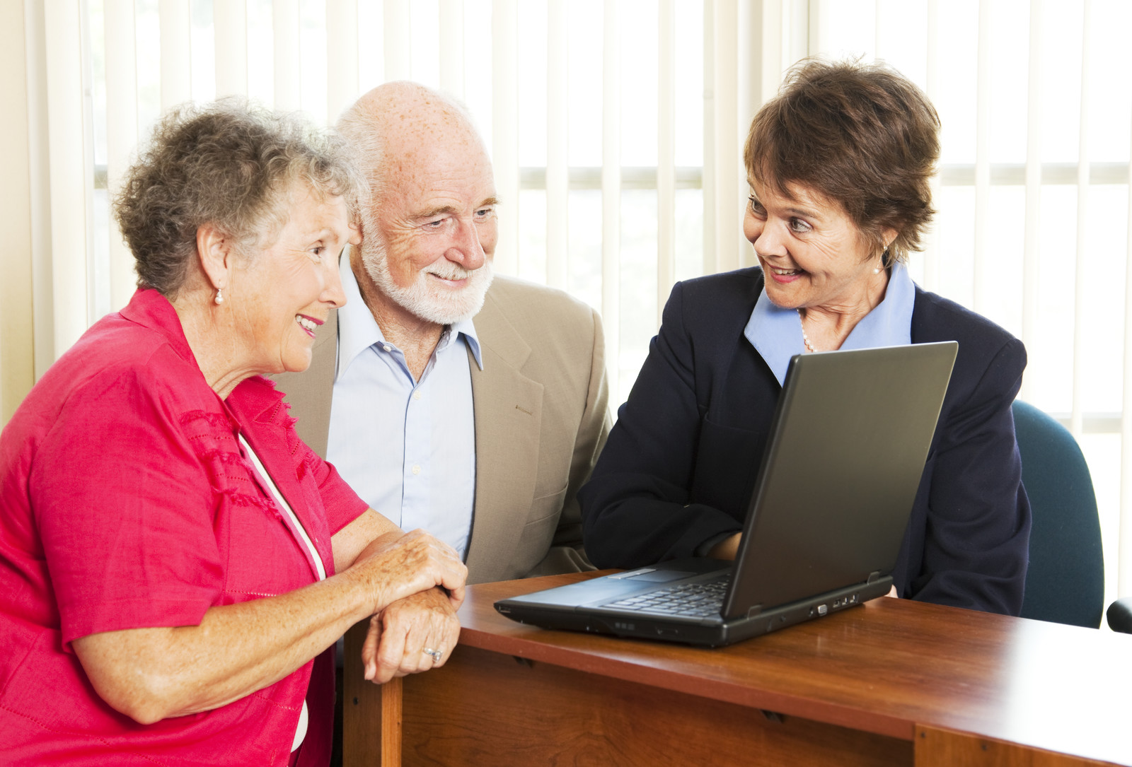 Persuasive sales woman pitches an investment opportunity to a senior couple