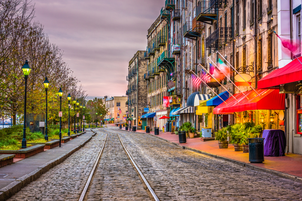 Brightly colored restaurants and bars lining one side of a Savannah street, with lights and trees on the other side
