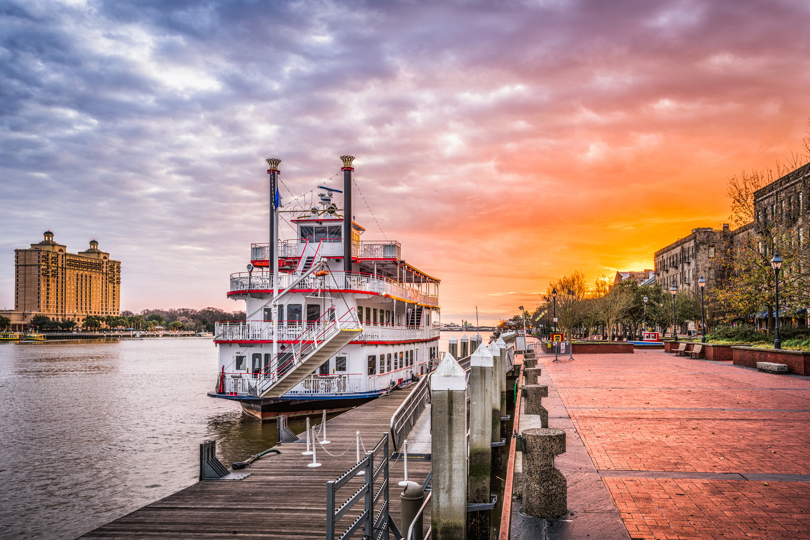 Places to Retire in Georgia -Savannah, georgia, riverfront with a paddleboat docked alongside the promenade at sunrise.