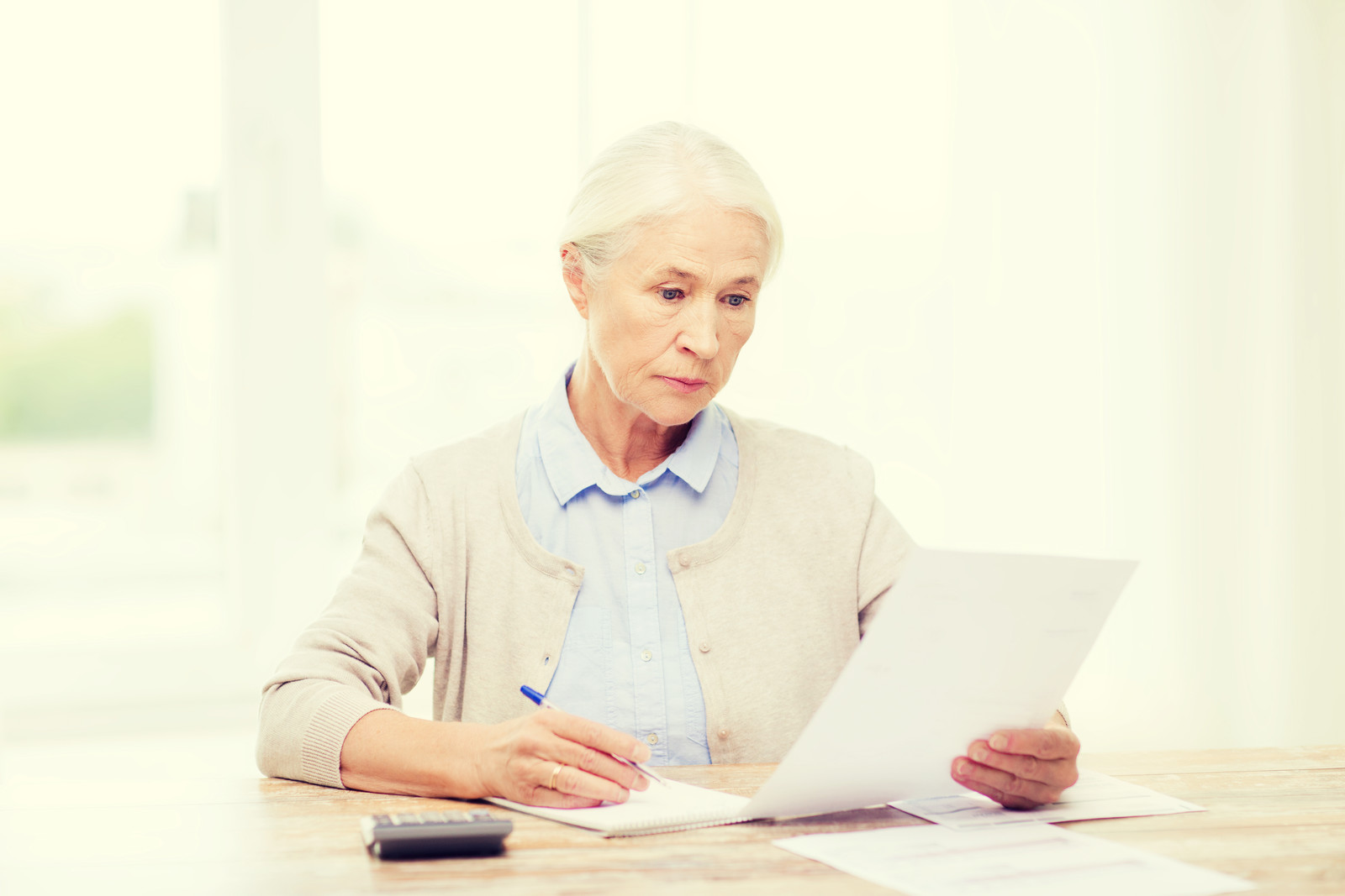 Senior woman reviewing a contract and taking notes