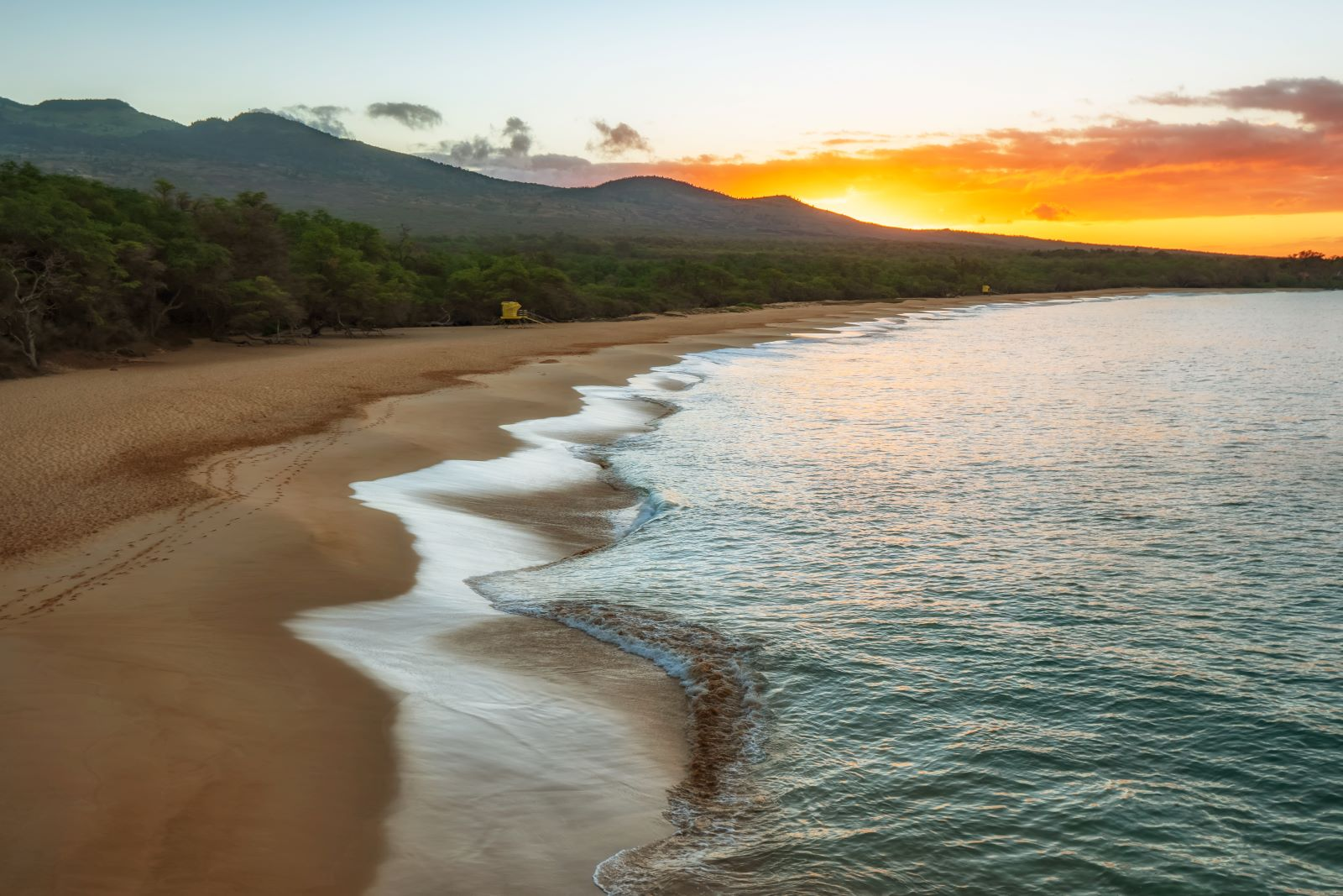 Places to Retire in Hawaii - Sandy beach at sunset showing the blue water gently lapping at the shore with trees along the beach and mountains in the background