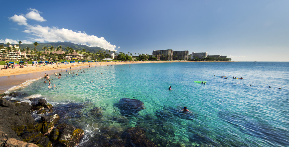 The beach at Kaanapali Hawaii where the water is blue and clear and various people can be seen in the water