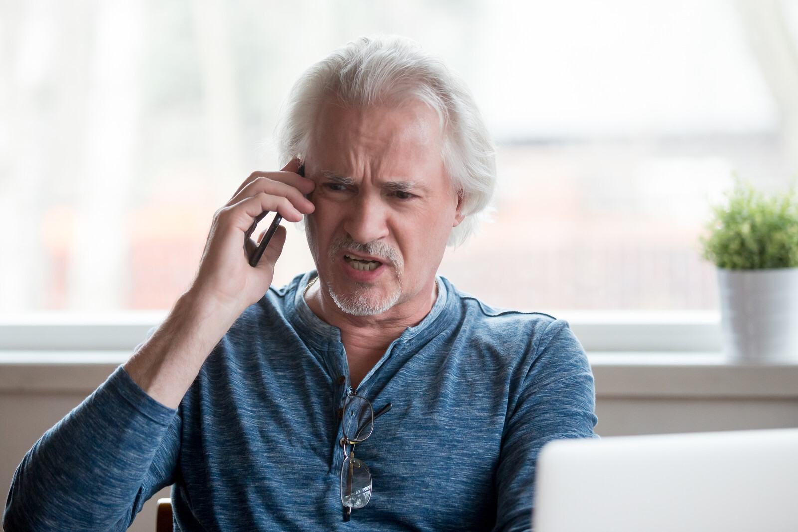 Upset senior man on the phone in front of laptop - represents a man reporting an annuity scam