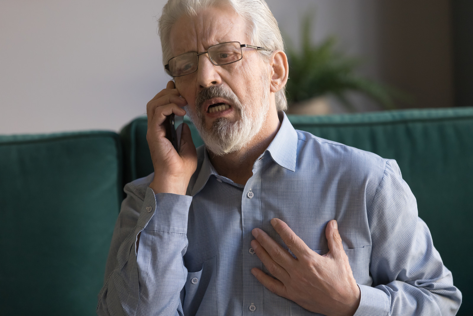 Older man sitting on couch looking distraught on the phone