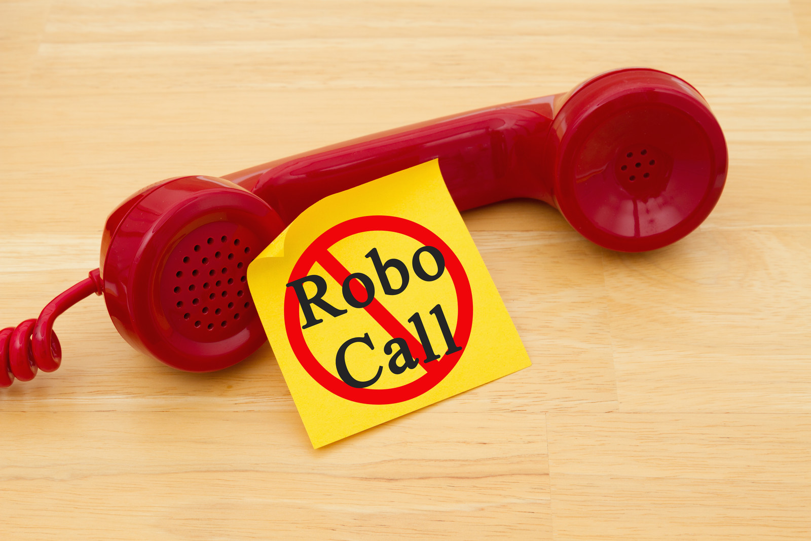 retro red phone handset with a yellow sticky note and text  that says robocall with the red circle with a line through it over the top of the words
