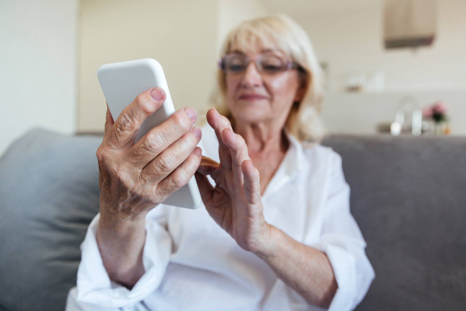 senior woman pressing numbers on her phone while sitting on her couch