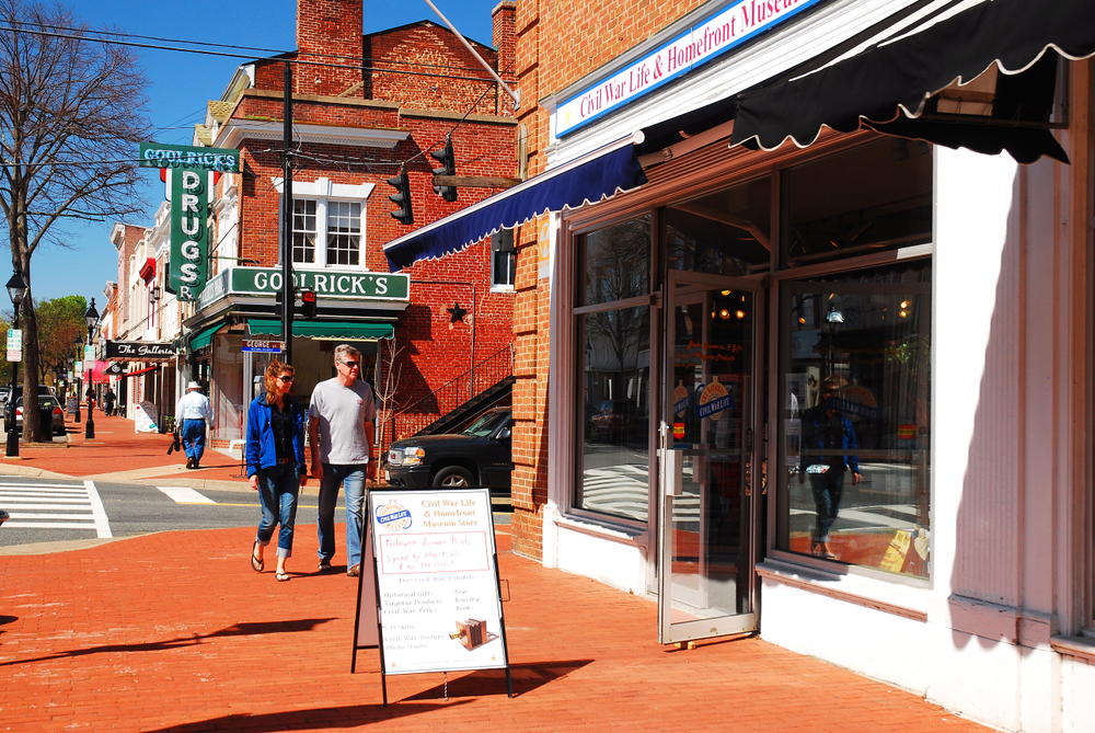 A couple walks through the brightly colored streets of Fredericksburg Virginia along an orange brick road next to historic buildings
