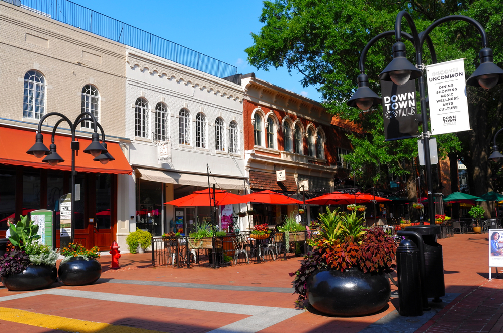 A downtown mall in Charlottesville Virginia showing brightly colored canopies, old-fashioned streetlights, and a bright blue sky