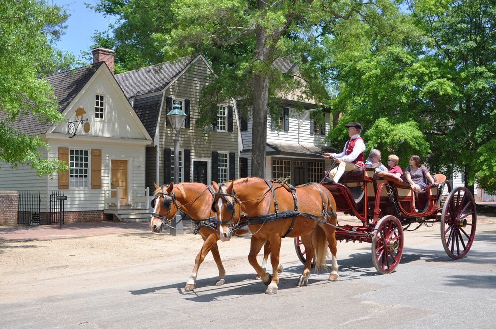 A horse drawn tour through Williamsburg Virginia, where the tour guide is dressed in a costume