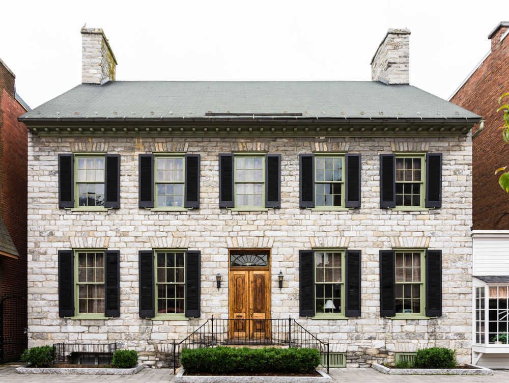 An old white building in the historic district of Winchester Virginia, with 9 windows and a door