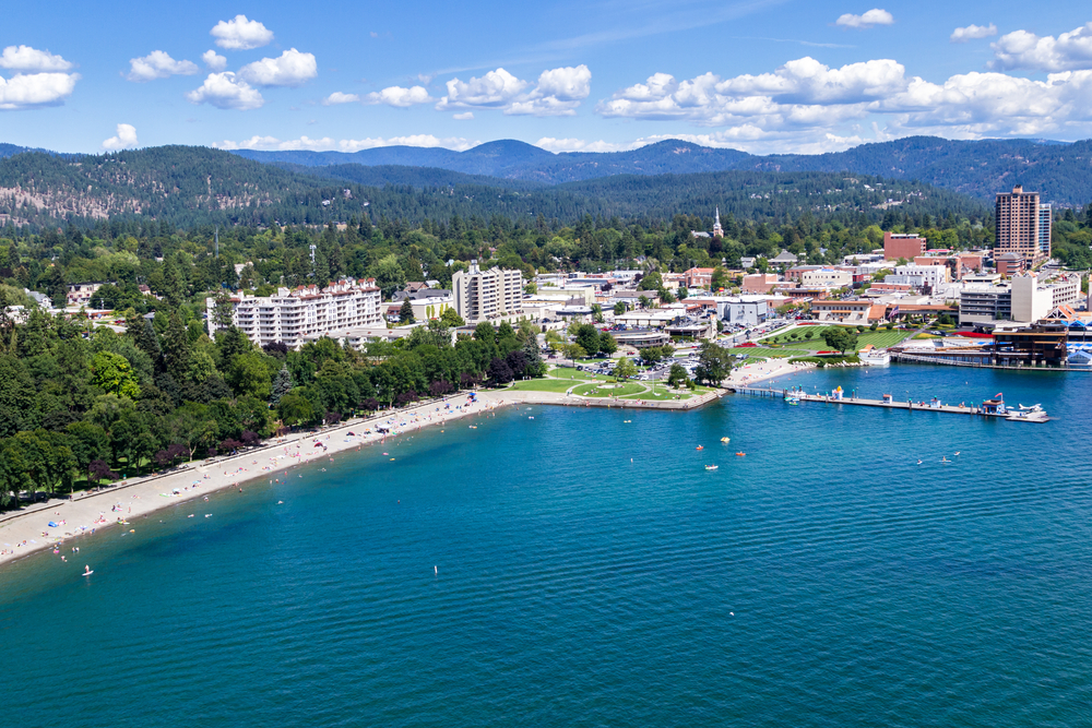 An aerial view of Coeur d'Alene Idaho showing the deep blue water, buildings, a cloudy blue sky and trees
