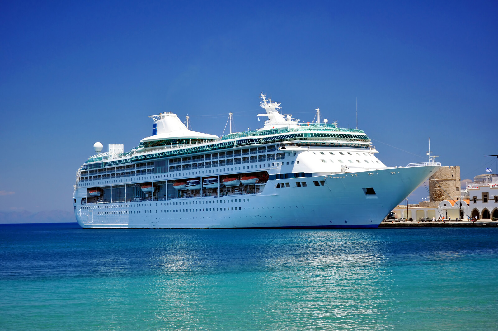 Large cruise ship sitting on the blue waters of the Mediterranean sea with blue skies