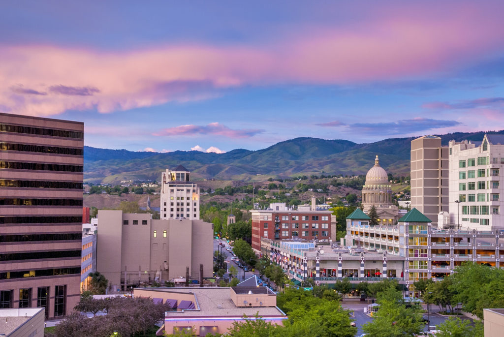 Places to Retire in Idaho - Downtown Boise Idaho at sunset with blue skies and pink clouds, with mountains in the background