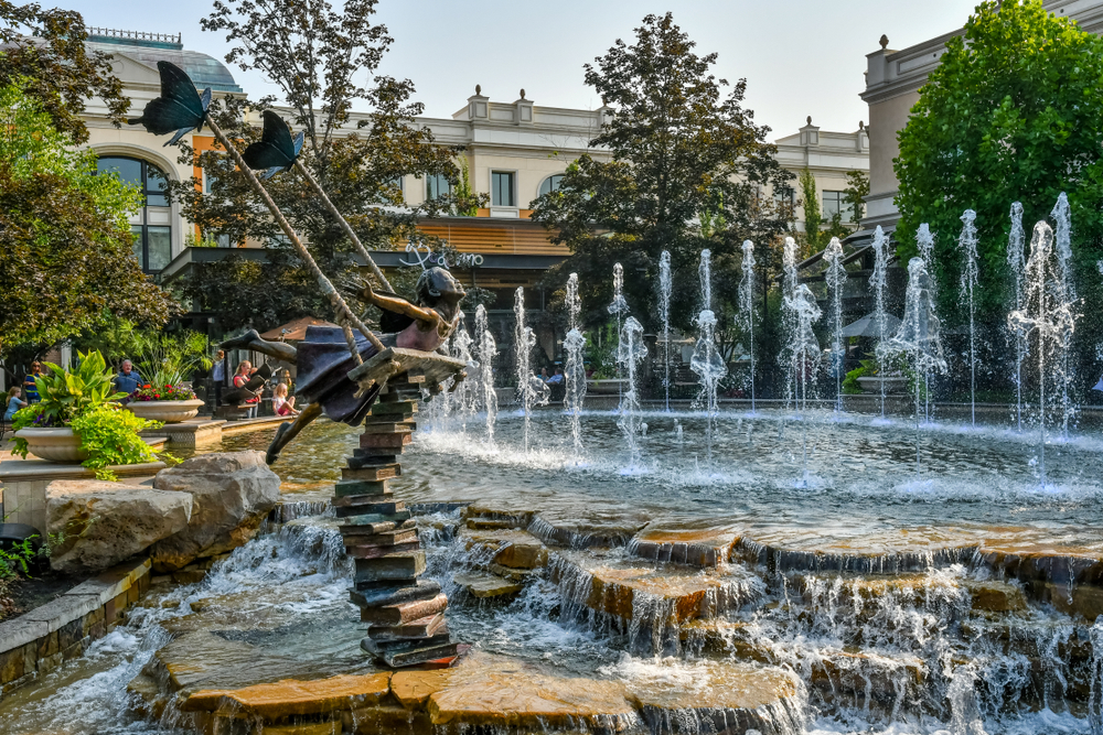 A statue of a girl in a fountain in Meridian Idaho where she appears to be swinging while on a stack of books