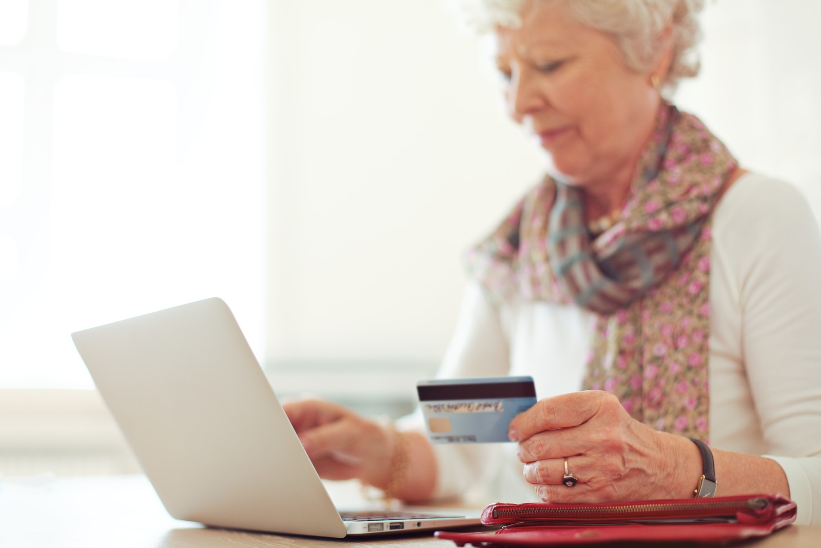 Senior woman at home on her laptop paying online with her credit card