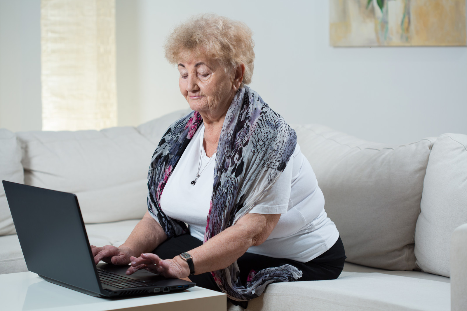 Senior woman on her couch typing on her laptop, symbolizes a woman reporting an IRS scam
