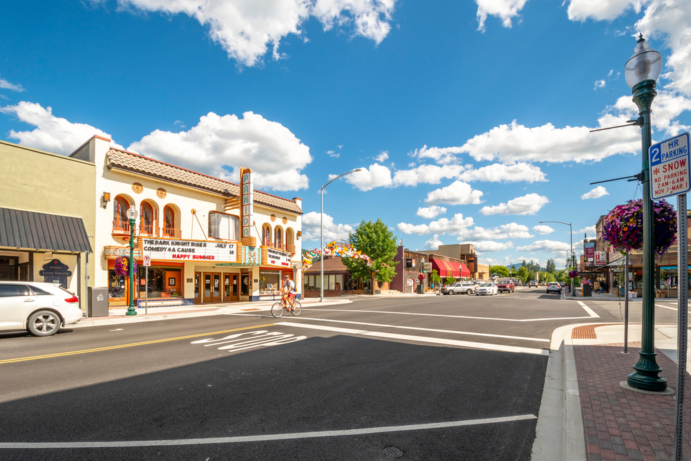 The main street in Sandpoint Idaho on a clear day, where there is sun on the ground and clouds in the sky