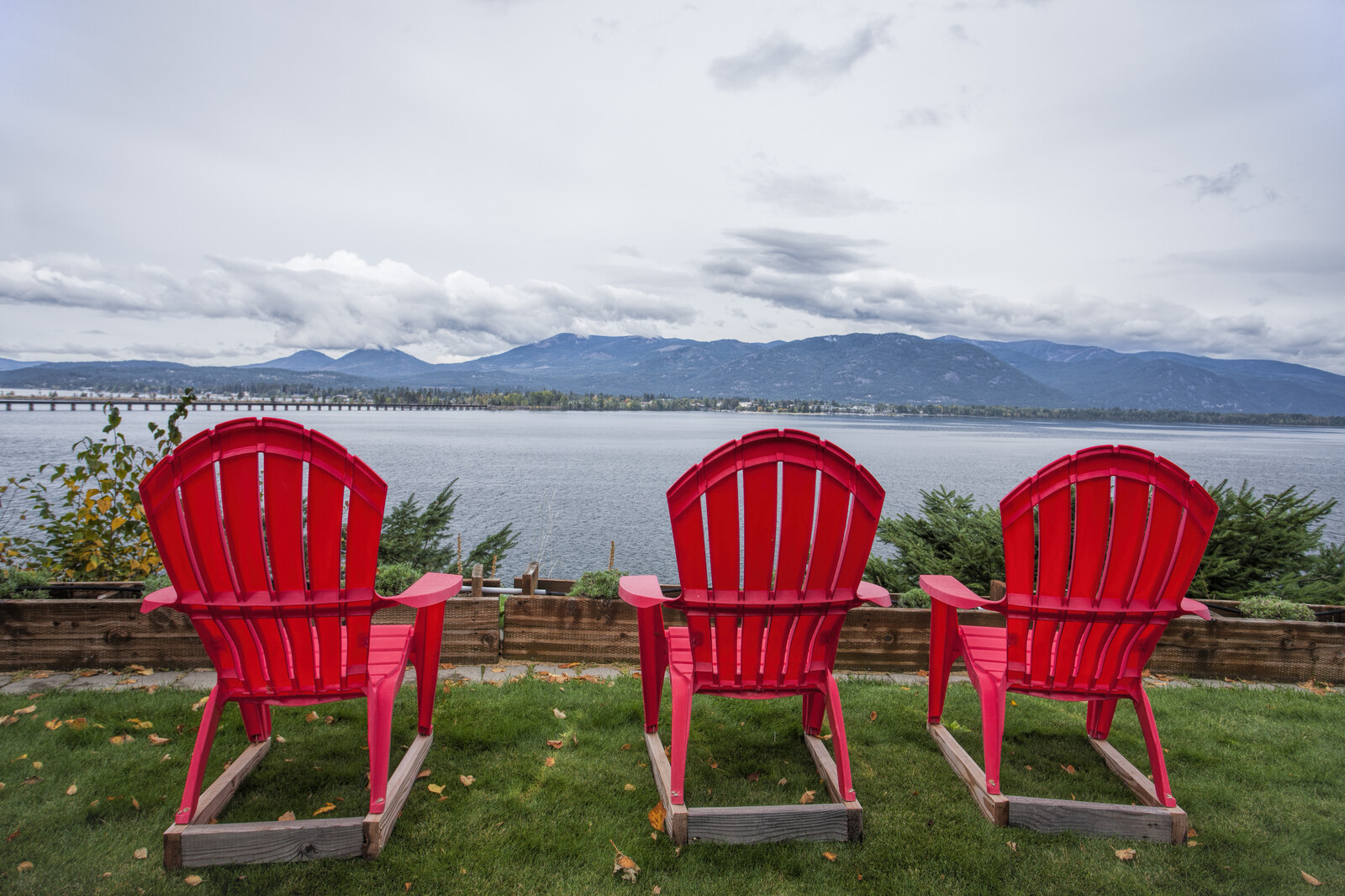 Three red lawn chairs sitting on green grass, overlooking the lake and mountain with grayish skies and white clouds