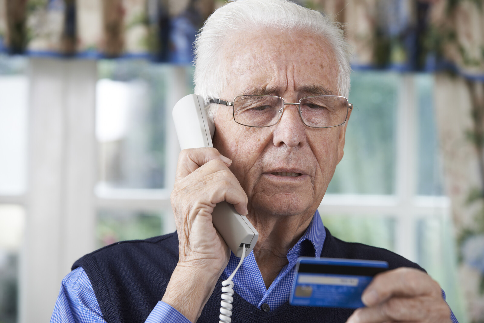 Senior man on the phone looking concerned giving his credit card number to the person on the other end of the line