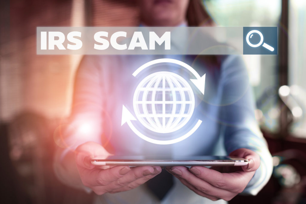 A woman holding a tablet with a hologram that says IRS scam