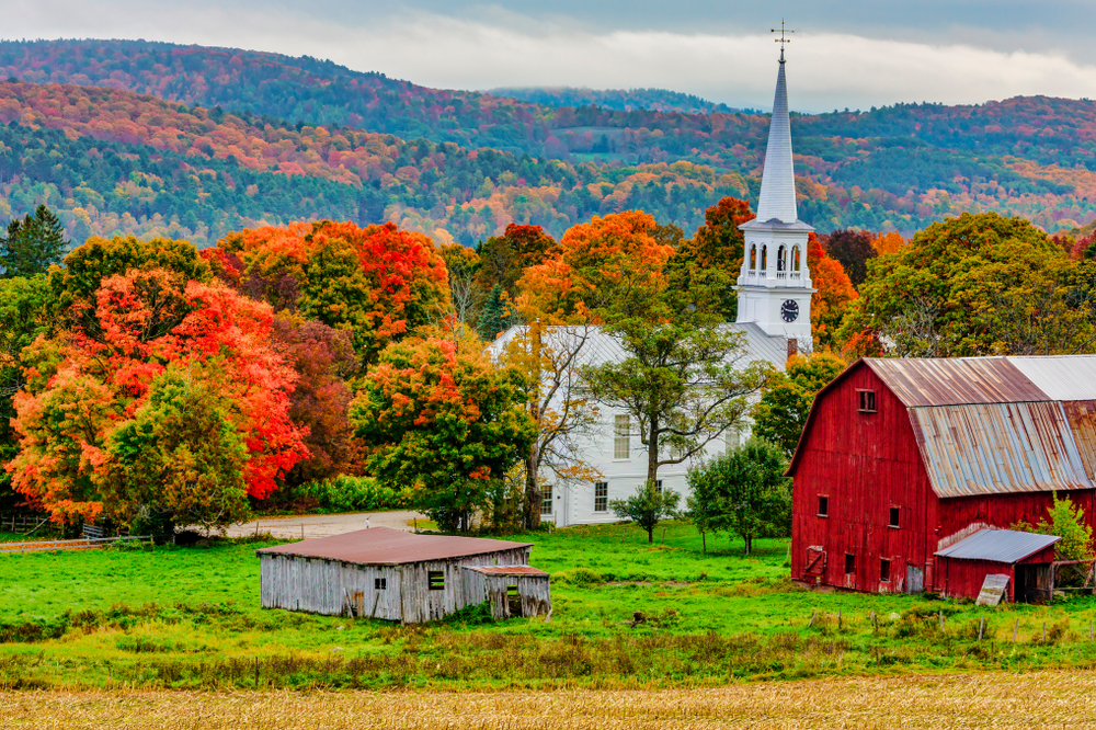 A barn and church in Woodstock Vermont in the Fall where the trees are vibrant colors