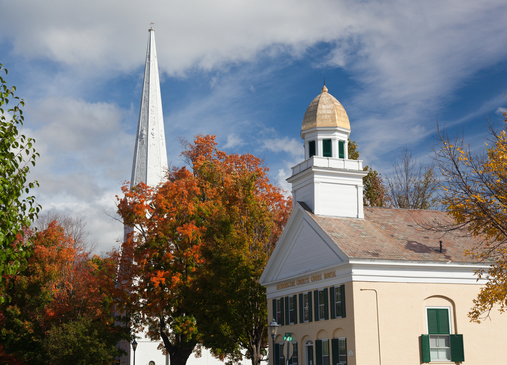A church building and steeple in Manchester Vermont against a blue cloudy sky