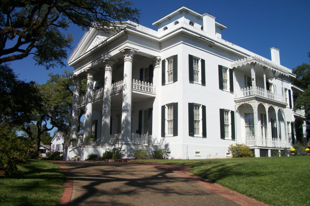 A historic plantation house in Hattiesburg Missisippi that is partly shaded by a tree