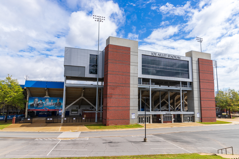 The outside of a stadium located in Ruston Louisiana with the blue sky and clouds behind it and a parking lot in front