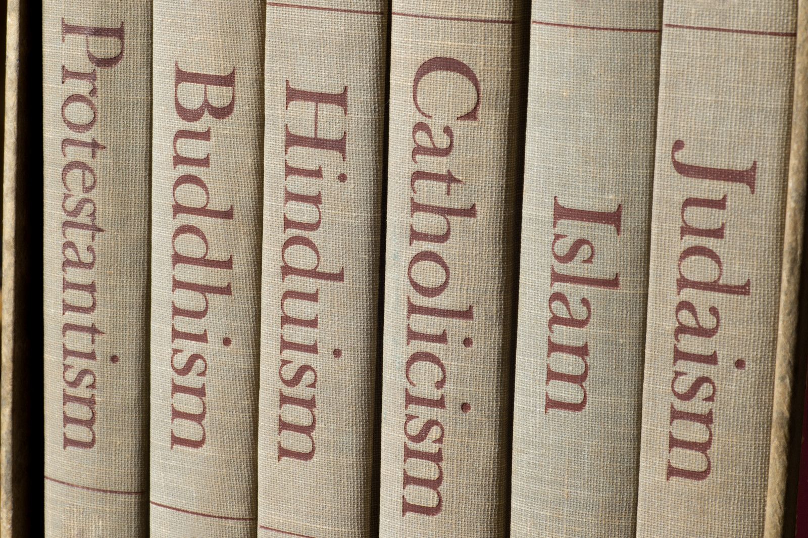 Religious Scams - Tan Book with brown writing with the spines listing major world religions