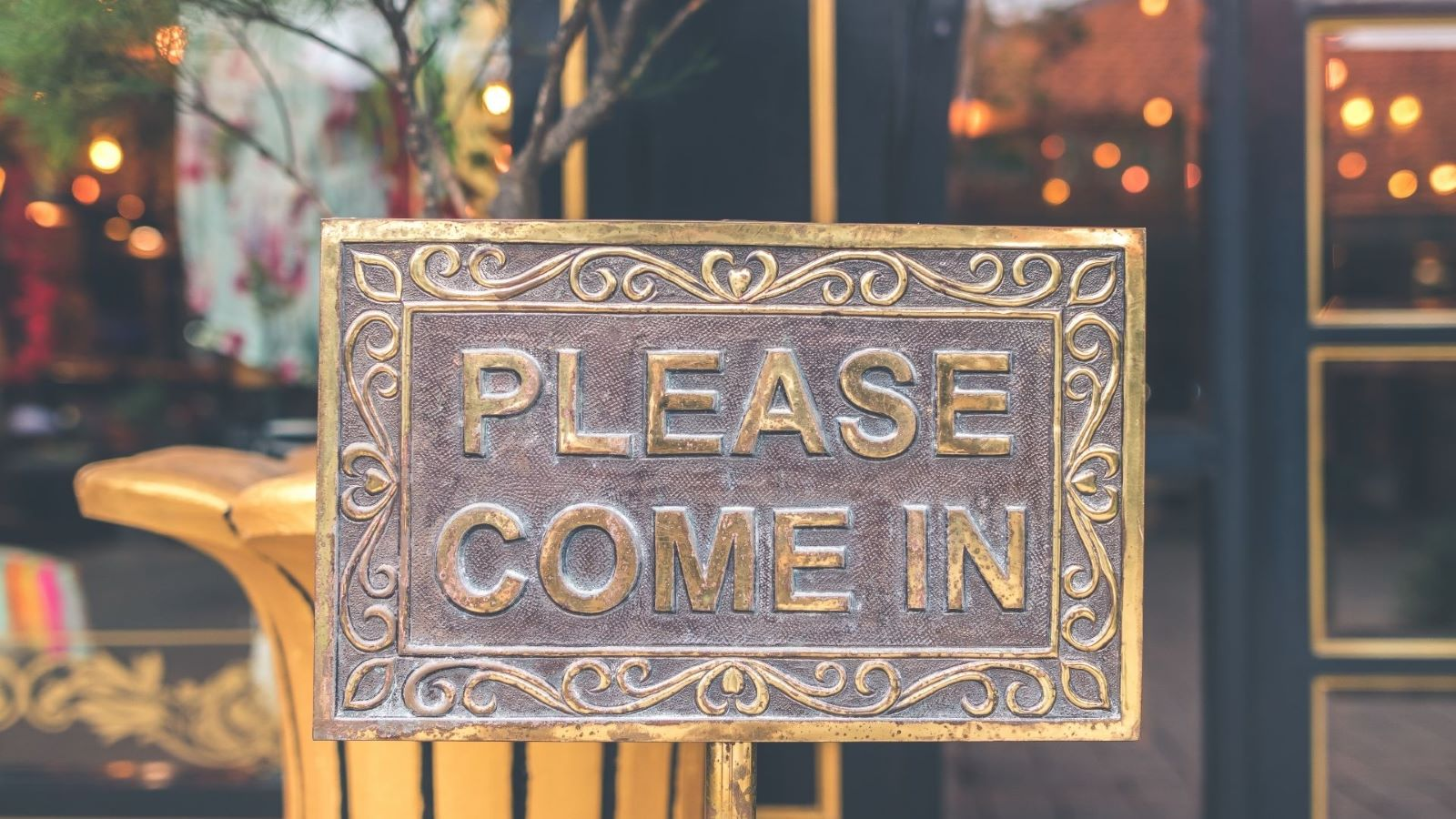 """A welcoming brass ornate sign that says """"Please Come in"""""""