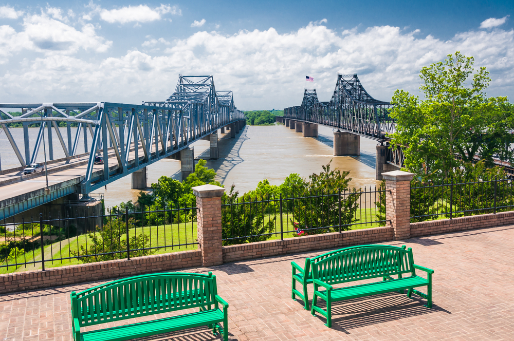 Two famous bridges in Vicksburg Mississippi with two green benches and some greenery in front of them
