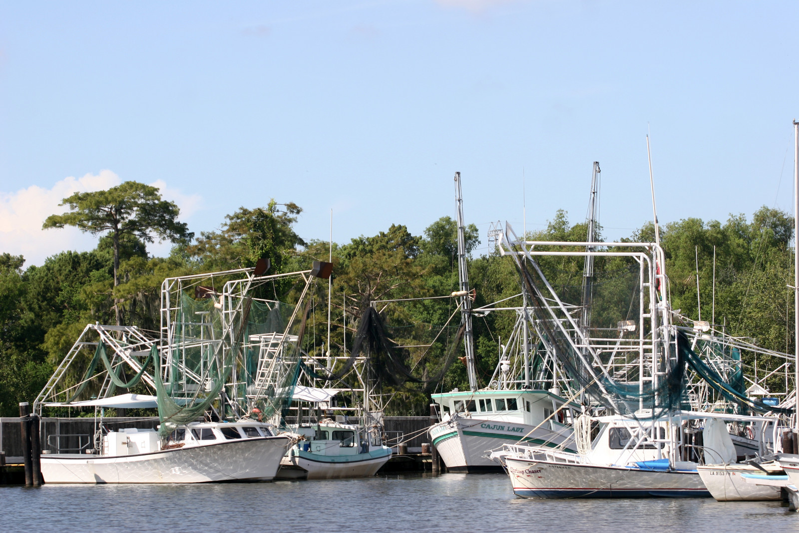 Top 5 Places to Retire in Louisiana - Fishing boats in a New Orleans Marina on a sunny day with blue skies