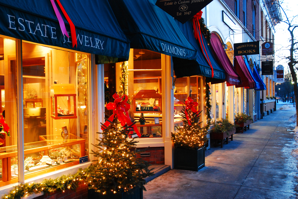 Jewelry stores in Woodstock Vermont in the early evening with their lights on and Christmas trees