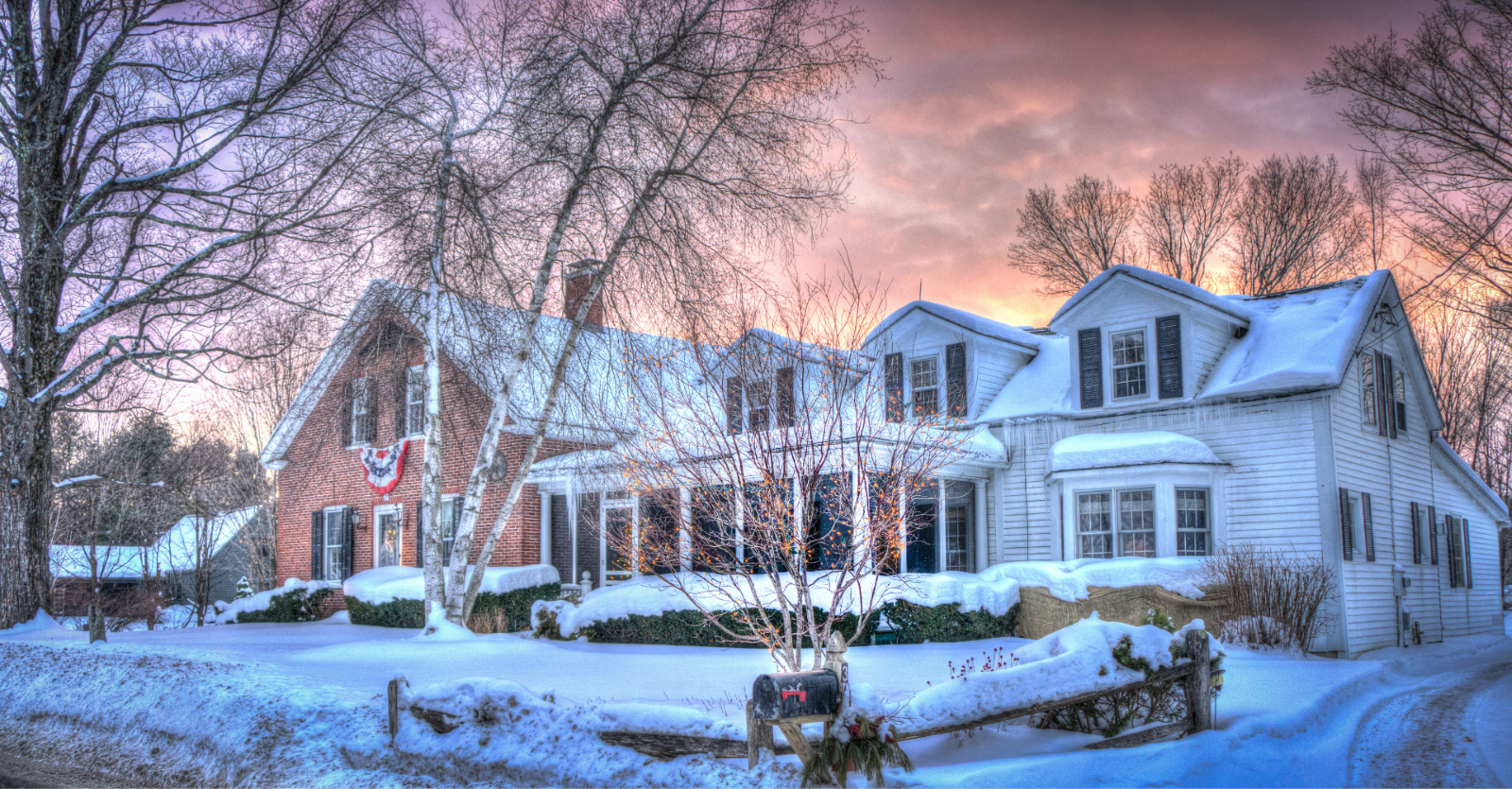 Winter day at sunset with pink and purple hued clouds over a suburban street with new england style homes lining the streets