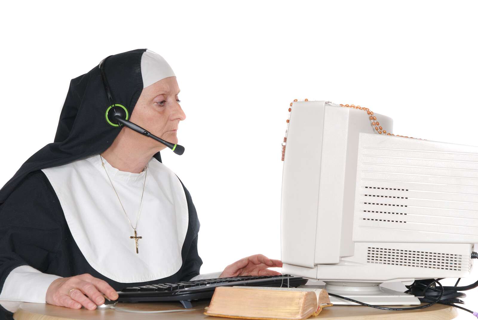 Middle aged nun on computer wearing a headset - represents the church ordering equipment