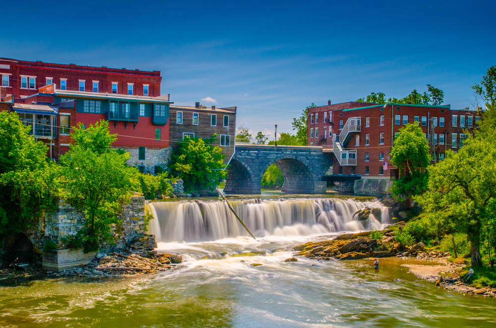 Otter Falls in the city of Middlebury Vermont showing old buildings and trees against a blue sky