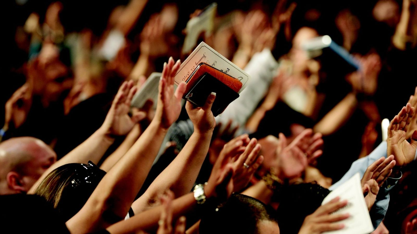 People raising their hands at a religious organization event