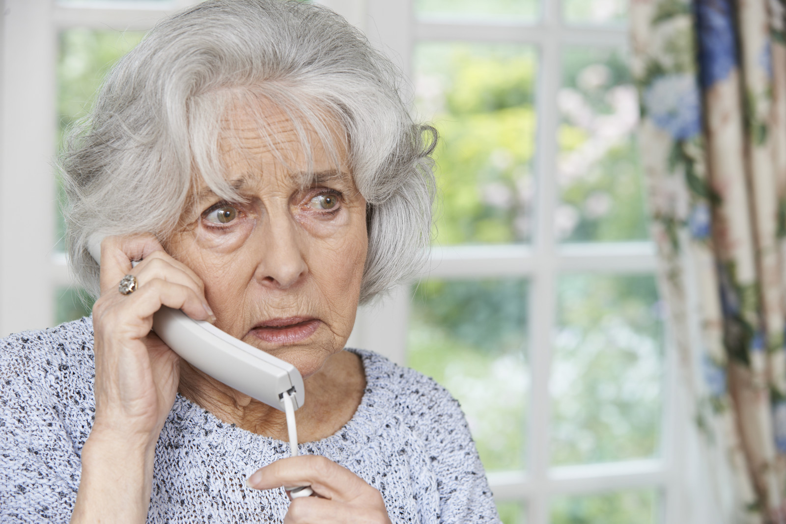 Scared senior woman on the phone in her home